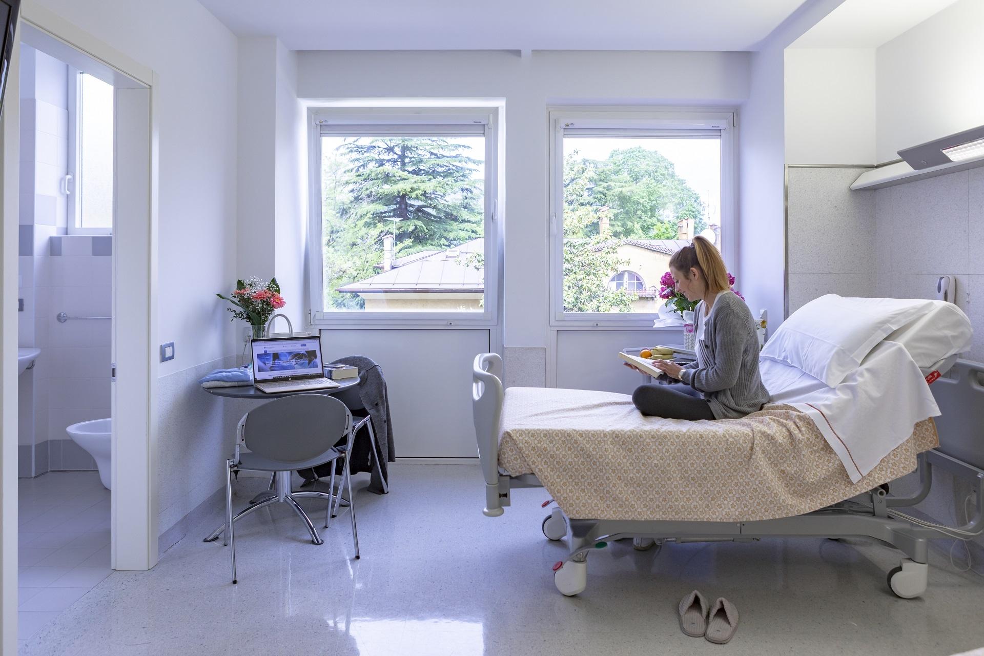 Ragazza seduta sul letto che legge un libro